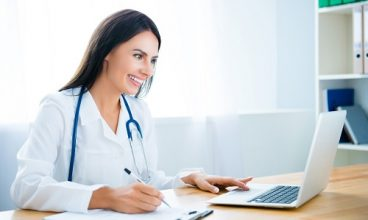 Young happy doctor using laptop and writing diagnosis